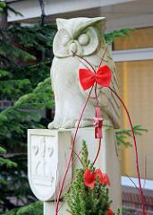 Skulptur Eule mit Quickborner Wappen, Weihnachtsdekoration mit roter Schleife.