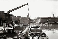 Binnenschiffe und Schuten haben an den Kais im Harburger Hafen festgemacht. Die Schiffer des Binnenschiffs GRETEL manövrieren ihr Schiff mit einem Bootshaken längsseits des Elbkahns. Ein Rollkran steht am Kai. (ca. 1938)