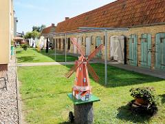 Hinterhof mit Schuppen / Holztüren - Wäsche ist zum Trocknen in der Sonne aufgehängt; Modellwindmühle im Vorgarten.