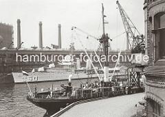 Im Vordergrund rechts das Verwaltungs-Ziegelgebäude der Fruchtschuppen im Baakenhafen. Am vorderen Kai des Magdeburger Hafens liegt ein Küstenmotorschiff das auf seinem Deck Fässer geladen hat. ( ca. 1934 )