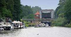 Schleuse in Mirow - Teil der Müritz Havel Wasserstrasse; technisches Denkmal / Höhenunterschied von 3,50m. Sportboote warten am Ufer - andere fahren in die Schleusenkammer ein - grünes Signallicht.