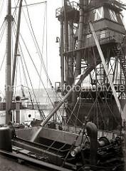 Der Getreideheber schüttet das aufgesaugte Getreide über ein Auslaufrohr in den Laderaum des Massengutfrachters im Hamburger Hafen / Kaiserkai. (ca. 1934)