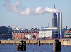 Heizkraftwerk Hamburger Hafencity mit rauchenden Schornsteinen, dahinter der Turm der St. Michaeliskirche - im Hintergrund Speichergebäude in der Speicherstadt / Freihafen. ( ca. 2001 )