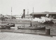 Das Frachtschiff CHORZOW liegt vor dem Schuppen 1 am Sandtorkai des Sandtorhafens. Mit zwei Schiffen im Schlepp fährt der Schlepper PAULINE der Fa. Harms & Sohn Hafenbecken hinein. (ca. 1934)
