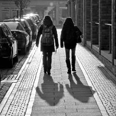 Gegenlichtaufnahme in Schwarz-Weiss; Fussgängerinnen mit langem Schatten, parkende Autos in der Bahnhofstrasse von Quickborn.