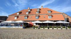 Hornscher Speicher - historische Architektur am Hafen von Neustadt in Holstein - Restaurant mit Sonnenschirmen, Kopfsteinpflaster.
