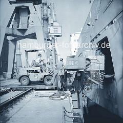 Über eine Ladeluke belädt ein Gabelstapler ein Frachtschiff am Burchardtka im Hamburger Hafen. (ca. 1972 )