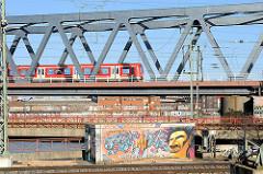 Eisenbahnbrücke über den Oberhafenkanal - ein S-Bahnzug fährt Richtung Veddel; im Hintergrund Speichergebäude am Billehafen in Hamburg Rothenburgsort / Grafitti mit gestrecktem Mittelfinger: Welcome in Hamburg.
