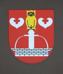 Quickborner Wappen - Brunnen mit goldener Eule, zwei silberne Seeblätter.