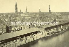 Luftaufnahme vom Sandtorhafen / Sandtorkai, und Brooktorviertel im historischen Hamburg - Wohnhäuser hinter den Kaischuppen am Sandtorkai, Frachter und Schuten  liegen am Kai. Kirchtürme der Hansestadt Hamburg. ( ca. 1870 )