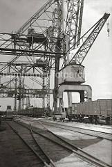 Am Kohlekai des Harburger Seehafens stehen offene Güterwagen unter dem Kohlekran und dem Portalkran. Ein Kohlefrachter liegt am Kai und die Kohleladung wird gelöscht - einer der Greifer schwebt gerade über einem der Güterwagen. (ca. 1938)