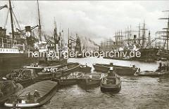 Historisches Foto vom Hansahafen in Hamburg -  Schuten und Elbkähne liegen mit Waren / Frachtgut an Dampfschiffen, Frachtern - in der Mitte des Hafenbeckens sind die Masten von Segelschiffen zu erkennen. (ca. 1925)