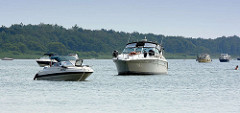 Sportboote, Motorboote liegen am Ufer des Fleesensees in der Sonne vor Anker.