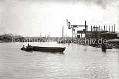 Eine Schute wird von der Barkasse HERTA aus dem Harburger Seehafen 3 auf die Süderelbe geschleppt; der Ewerführer steht auf dem Heck seines Lastkahns. Ein Seeschiff und ein Frachtsegler liegen an den Dalben des Hafenbeckens. (ca. 1938)