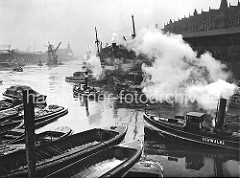 Frachter liegen am Sandtorkai, Schuten haben längsseits fest gemacht - ein Schlepper unter Dampf kommt vom Brooktorhafen und fährt in den Sandtorhafen ein. Vor dem Kaiserkai wird ein Kohleheber von zwei Schleppern gezogen. (ca. 1932)