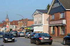 Einzelhäuser, Geschäfte - dichter Strassenverkehr auf der Kieler Strasse in Quickborn; im Hintergrund der Kirchturm der Marienkirche.