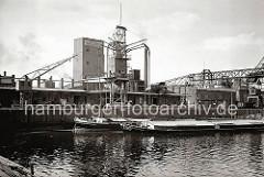 Zwei Elbkähne liegen vor der Privat-Kai-Anlage der Hamburger Getreide-Lagerhaus Aktiengesellschaft, Zweigniederlassung Harburg. Die Saugvorrichtungen des Getreidehebers führen in den abgedeckten Laderaum des Binnenschiffs. (ca. 1938)