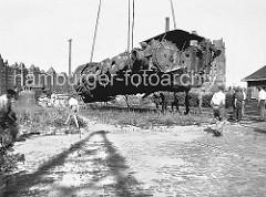 Eine im Krieg zerstörte Lokomotive wird 1948 von einem Kran im Sandtorhafen geborgen; im Hintergrund die Gebäude der Speicherstadt am Brooktorkai - rechts ist ein Ausschnitt des Kaispeichers B zu erkennen. (1948)