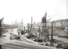 Ein Massengutfrachter hat mit dem Heck am Kai im Sandtorhafen fest gemacht - auf der Steuerbordseite liegt ein pneumatischer Getreideheber, der das Getreide mittels eines Luftstroms über die Saugleitungen transportiert. (ca. 1934)