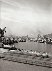 Blick in den Sandtorhafen Richtung Elbe - im Hintergrund lks. der Kaispeicher und rechts hinter den Schiffen am Sandtorkai die Dächer der Speicherstadt. Ein Schwimmkran verlässt mit eigenem Antrieb den Sandtorhafen. (ca. 1934)