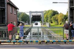 Schleuse in Mirow - Teil der Müritz Havel Wasserstrasse; technisches Denkmal / Höhenunterschied von 3,50m. Passanten beobachten von der Strassebrücke den Schleusenvorgang - ein Sportboot fährt in die Schleusenkammer ein.