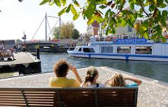 Ein Ausflugsschiff der Blau Weissen Flotte mit Touristen an Bord an der geöffneten Drehbrücke in Malchow - Touristen fotografieren das Fahrgastschiff.