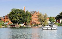 Auf Durchfahrt wartendes Sportboote auf dem Malchower See, im Hintergrund die Ruine der alten Weberei / Spinnerei / Tuchfabrik  in Malchow; erbaut 1908, 1990 stillgelegt.