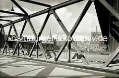 Blick durch die Eisenträger der Baakenbrücke, die den Magdeburger Hafen überspannt. Im Hinter- grund die Bogenkonstruktion der Magdeburger Brücke, rechts davon der Kaispeicher B.  ( ca. 1932 )