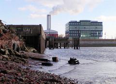 Dalmannkai im Hamburger Grasbrookhafen - Neubau eines Bürgebäudes am Grosser Grasbrook - dahinter die Schornsteine vom Hafencity-Kraftwerk.