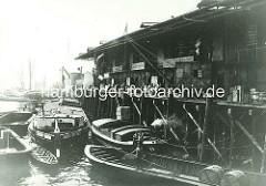 Schuppen der Vereinigten Elbschiffahrts-Gesellschaft im Magdeburger Hafen, Hafenbecken im Hamburger Hafen. Elbkähne liegen an der Kaianlage - ein Kran hebt eine Kiste, im Vordergrund ein Ewerführer mit Peekhaken auf seiner Schute - zwei Fässe
