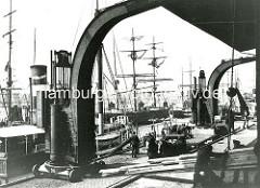 Ladebühne / Kaianlage am Strandkai im Hamburger Hafen - altes Foto von der Hafenarbeit; ein Frachter löscht Bretter - Schuppenarbeiter lenken die Hieve der Tannenbretter auf einen Rollwagen. (ca. 1905 )