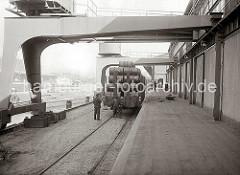 Ein mit Fässern beladener Güterzug steht an der Laderampe eines Schuppens am Kaiserkai des Sandtorhafens. Darüber laufen die Portale der Krane. (ca. 1934)