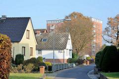 Einzelhäuser mit Spitzdach; Vorgarten an einer schmalen Nebenstrasse, mehrstöckiger Wohnblock im Hintergrund. Bilder aus Quickborn, Kreis Pinneberg.