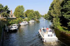 Ein Sportboot kommt aus der Schleuse am Baalensee und fährt in die Schleusenhavel in Fürstenberg ein. Weitere Motorboote warten am Ufer auf die Schleusung.
