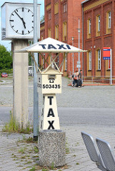 Alte Taxirufsäule mit Dach und Aufschrift Taxi - Normaluhr am Bahnhof Rathenow.