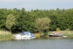Sportboote haben am Ufer der Havel festgemacht - die Passagiere geniessen die Sonne am Waldesrand.