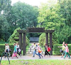 Parkstrasse in Hagenow -  Hölzernes Portal -  Eingang zum Ehrenfriedhof für Häftlinge aus dem KZ Wöbbelin.