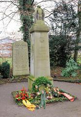 Gedenkstätte beider Weltkriege im Quickborner Ortsteil Renzel, Friedenstrasse. Stele mit Adler und Inschrift, Kränze.