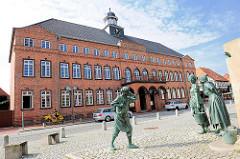Fiek'n Brunnen vor dem Rathaus von Hagenow, Rathausplatz / Lange Strasse. Der Brunnen 2007 errichtet, Künstler Bernd Streiter - ein Schusterjunge belauscht zwei Frauen beim Tratschen. Im Hintergrund das Hagenower Rathaus.