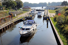 Ein Sportboot kommt aus der Schleuse am Baalensee und fährt in die Schleusenhavel in Fürstenberg ein; weitere Motorboote liegen noch in der Schleusenkammer.