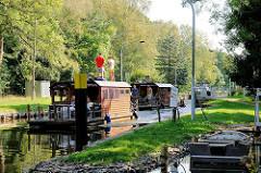 Hausboote verlassen die Schleuse Steinhavelmühle an der Steinhavel von Fürstenberg ( Havel ) und fahren auf der Havel Richtung Menowsee.