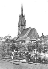 Ufer vom Hafen in Rathenow, Bug eines Binnenschiffs / Lastkahn - Gartenlauben am Havelufer; St. Marien Andrea Kirche zwischen Hausdächern der Stadt.