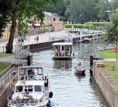 Blick über die Stadtschleuse von Rathenow an der Havel - Boote fahren in die Schleusenkammer ein - im Hintergrund der Stadthafen für Gastlieger mit Restaurant und Hotel.