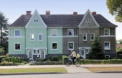 Altes einstöckiges Doppelhaus mit unterschiedlicher Fassadendekoration; verwaschener Rauhputz und mintgrüne Hausfassade / alt + neu.
