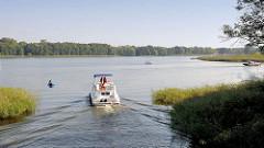 Ein Motorboot fährt auf der Havel in den Schwedtsee ein; re. im Hintergrund die Mahn- und Gedenkstätte Ravensbrück am Seeufer.
