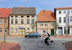 Mehrstöckige Wohnhäuser, teilweise leerstehend - Lange Strasse in Hagenow; Auto und Fahrradfahrer in Fahrt.
