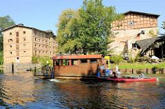 Ein Hausboot und Kanu auf der Havel an der Steinhavelschleuse - am Ufer die unter Denkmalschutz stehenden Gebäude der historischen Steinmühle.