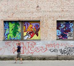 Unverputze Mauersteine, Ziegelfassade - bunte Wandmalerei, Fussgänger; Bilder aus der Stadt Rathenow, Landkreis Havelland.