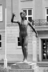 Bronzeskulptur - Junge / Fackelträger; vor der Grundschule  am Weinberg in Rathenow; Bildhauer Karl Mertens, 1958.