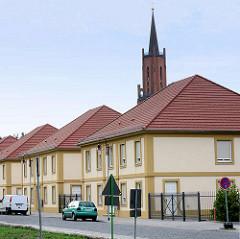 Kirchturm der Sankt Marien Adreas Kirche auf dem Kirchberg in Rathenow.  Rechteckige einstöckige Wohnhäuser / Neubauten mit Walmdach.